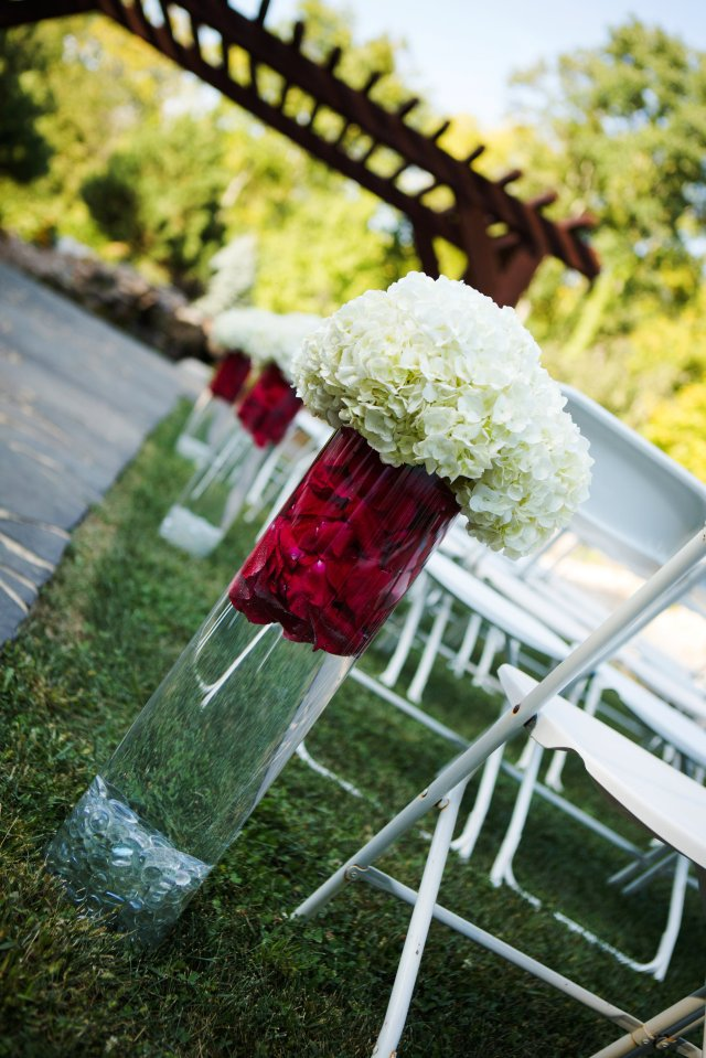 The ceremony site featured tall, glass vases with red flower petals and white hydrangeas.