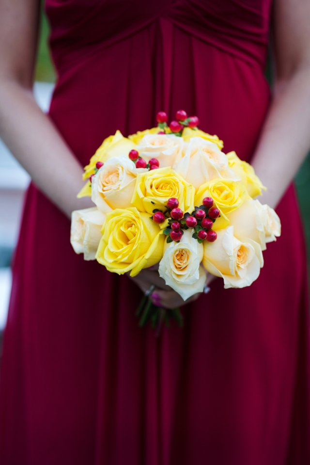 The bridal party carried yellow and peach roses with red hypericum berries.